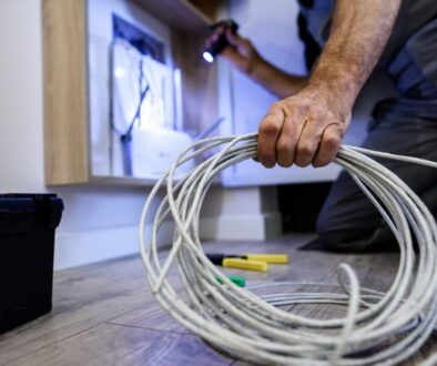 Close up shot of hand of aged electrician, repairman in uniform working, fixing, installing an ethernet cable in fuse box, holding flashlight and cable