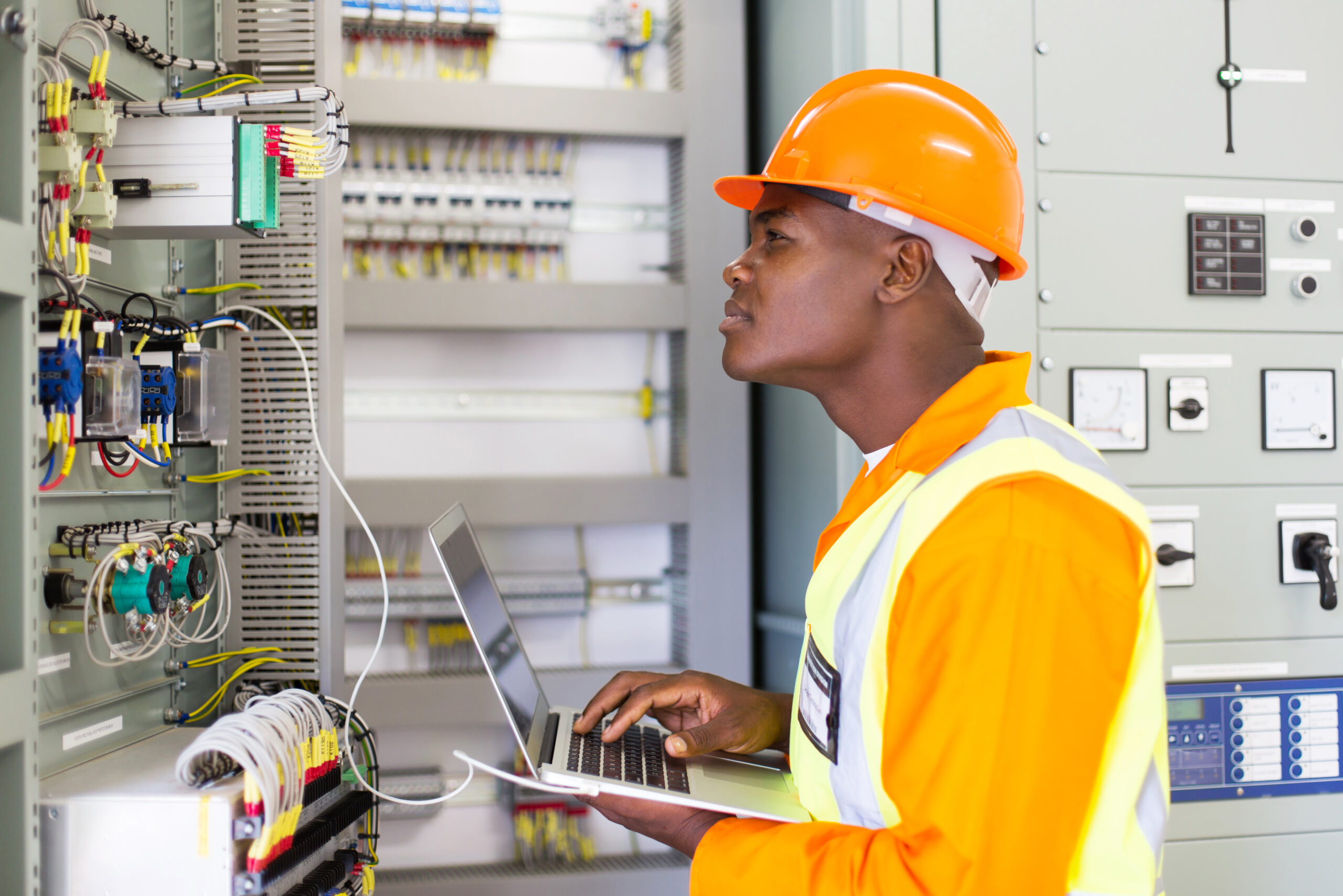 african industrial electrician working in control room